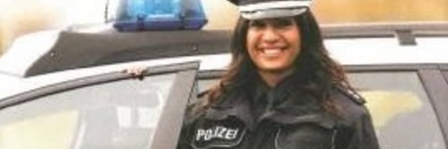 Polizistin mit Migrationshintergrund vor einem Polizeiauto stehend